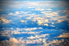 The early morning rays of the sun rising gave the sky a blue ting.. At the center we could see the first sights of the snow capped peaks from the plane