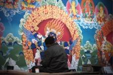 An artist working on renovating the mural paintings inside the Hemis monastery